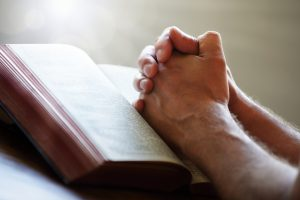 bigstock-hands-folded-in-prayer-on-a-ho-47921843